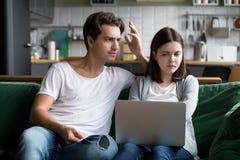 Gestörter Ehemann, der die frustrierte Frau vergeudet Geld auf onl verurteilt stockbild