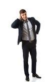 Gestörter Geschäftsmann, der sein Ohr bedeckt Stockfoto