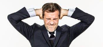 Gestörter junger Geschäftsmann, der seine Ohren vom Unternehmensburnout bedeckt Lizenzfreie Stockbilder