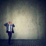 Gestörter Mann, der Ohren mit den Fingern frustriert mit lauten Geräuschen verstopft lizenzfreies stockfoto