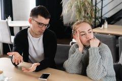 Gestörter Mann, der versucht, etwas seiner Frau zu erklären stockfotografie