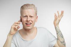 Gestörter Mann mit dem die Stirn gerunzelten Gesicht, das unangenehme Nachrichten am Handy empfängt Lizenzfreies Stockbild