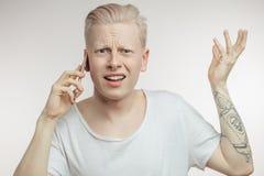 Gestörter Mann mit dem die Stirn gerunzelten Gesicht, das unangenehme Nachrichten am Handy empfängt Lizenzfreie Stockfotos
