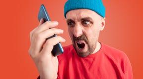 Gestörter Mann mit verzerrtem Gesicht schreiend an seinem Mobiltelefon stockfotos