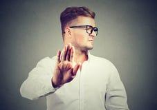 Gestörter verärgerter Mann mit der schlechten Haltung, die Gespräch zum Handzeichen gibt stockfotografie