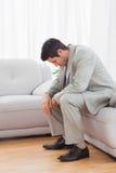 Gestörtes buinessman, das auf dem Sofa senkt seinen Kopf sitzt Stockbild