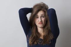 Gestörtes Mädchen 20s, das oben ihr Haar für Frustration oder Widerspruch verwirrt Stockfotos