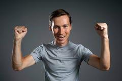 Gest sukces Uśmiechnięty mężczyzna w szarej koszulce z nastroszonymi rękami Obrazy Royalty Free