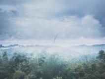 Gestalten Sie Berg und Wald im Nebel mit Himmel landschaftlich und bewölkt Hintergrund auf Sonnenschein Lizenzfreie Stockfotografie