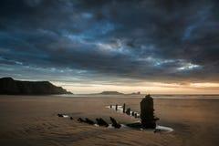 Gestalten Sie Bild des alten Schiffbruchs auf Strand bei Sonnenuntergang im Sommer landschaftlich Stockfotografie