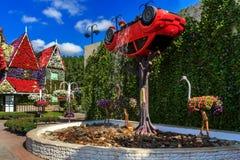Gestalten Sie Blumenanordnung mit einem Auto und einem Brunnen landschaftlich stockbild