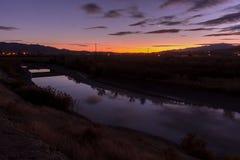 Gestalten Sie an der Dämmerung mit einer schönen Reflexion weg vom Wasser landschaftlich stockbilder