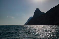 Gestalten Sie Foto von Felsen im Meer im Sonnenuntergang landschaftlich Stockbild