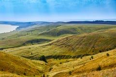 Gestalten Sie, grüne Hügel des Sommers und Fluss in den schönen Umgebungen landschaftlich Stockbilder