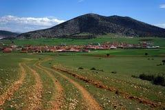 Gestalten Sie grünes Gras, Dorf, Bäume und Berge landschaftlich Stockbild