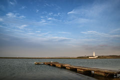 Gestalten Sie großen Himmel des Bildes mit Leuchtturm im Abstand und in der Anlegestelle landschaftlich Stockbild