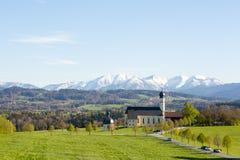 Gestalten Sie im Bayern, Deutschland, Kirche mit Bergen im Hintergrund landschaftlich Stockfotografie