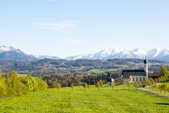 Gestalten Sie im Bayern, Deutschland, Kirche mit Bergen im Hintergrund landschaftlich Lizenzfreie Stockbilder