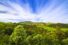 Gestalten Sie Landschaft des grünen Tales, des Hügels und des bewölkten blauen Himmels landschaftlich Stockbild
