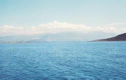 Gestalten Sie Meer und Berge mit Wolken im Abstand landschaftlich Lizenzfreies Stockbild