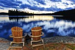 Holzstühle am Sonnenuntergang auf Seeufer Stockfotos