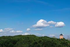 Gestalten Sie mit Bäumen, blauem Himmel, Wolken und einem Glöckchenglockenturm landschaftlich Lizenzfreie Stockfotos