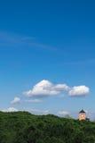 Gestalten Sie mit Bäumen, blauem Himmel, Wolken und einem Glöckchenglockenturm landschaftlich Stockbilder