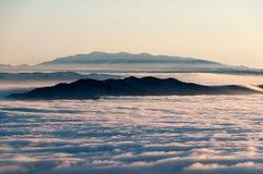 Gestalten Sie mit Bergspitzen und Wolken während der Winterzeit landschaftlich Stockfotografie