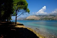 Gestalten Sie mit blauem Meer, Bäumen und Bergen landschaftlich stockfotografie