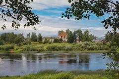 Gestalten Sie mit breitem russischem Fluss und den Ruinen eines alten Tempels landschaftlich Lizenzfreie Stockbilder