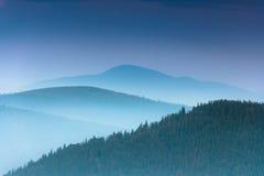 Gestalten Sie mit bunten Schichten Bergen und Dunsthügeln landschaftlich, die durch Wald bedeckt werden lizenzfreies stockbild