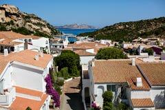 Gestalten Sie mit Dachspitzen und dem Meer in Sardinien landschaftlich Lizenzfreie Stockfotografie