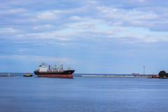 Gestalten Sie mit dem Schleppseilboots- und -frachtschiff landschaftlich, das in Seehafen hereinkommt Lizenzfreie Stockbilder