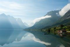 Gestalten Sie mit den Bergen landschaftlich, die im See und im kleinen Boot nahe dem Ufer, Norwegen sich reflektieren Stockfotos