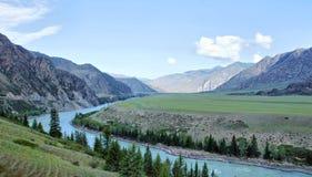 Gestalten Sie mit einem Fluss landschaftlich, der unter den Bergen fließt Lizenzfreie Stockbilder