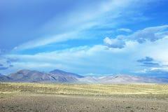Gestalten Sie mit einem Hochlandtal und -bergen im Abstand landschaftlich Stockfoto