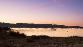 gestalten Sie mit einem Segelbootsegeln bei Sonnenuntergang auf den Ufern von einer Insel Galizien landschaftlich lizenzfreies stockfoto