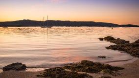 gestalten Sie mit einem Segelbootsegeln bei Sonnenuntergang auf den Ufern von einer Insel Galizien landschaftlich lizenzfreie stockfotos