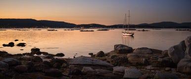 gestalten Sie mit einem Segelbootsegeln bei Sonnenuntergang auf den Ufern von einer Insel Galizien landschaftlich stockfotografie
