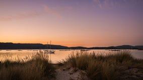 gestalten Sie mit einem Segelbootsegeln bei Sonnenuntergang auf den Ufern von einer Insel Galizien landschaftlich lizenzfreie stockbilder