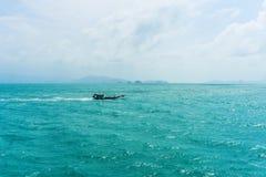 Gestalten Sie mit einer blauen Seeansicht, ein Schwimmen wenigen Bootes landschaftlich stockfoto