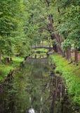 Gestalten Sie mit einer Brücke über Kanal im Palastpark landschaftlich Lizenzfreie Stockbilder