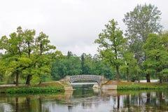 Gestalten Sie mit einer Brücke über Teich im Palastpark in Gatchina landschaftlich Lizenzfreies Stockfoto