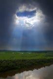 Gestalten Sie mit Fluss landschaftlich und durchlöchern Sie in den dunklen Wolken Lizenzfreie Stockfotografie