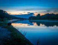Gestalten Sie mit Fluss und Wald auf einem Sonnenuntergang landschaftlich Stockbilder