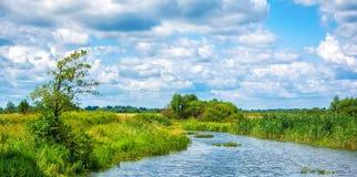 Gestalten Sie mit Fluss und Wolken im Himmel landschaftlich Lizenzfreie Stockfotografie