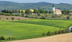 Gestalten Sie mit grünem Weizenfeld und -stadt in der Tschechischen Republik landschaftlich Lizenzfreies Stockfoto