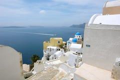 Gestalten Sie mit Häusern und Boot auf Santorini-Insel landschaftlich Lizenzfreies Stockfoto