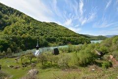 Gestalten Sie mit Kirche und Häusern nahe dem sterilen See von Geamana-Dorf, Apuseni-Berge landschaftlich Lizenzfreie Stockbilder