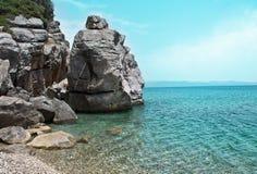 Gestalten Sie mit Küstenklippen und ruhigem See an einem sonnigen Tag landschaftlich Lizenzfreie Stockbilder
